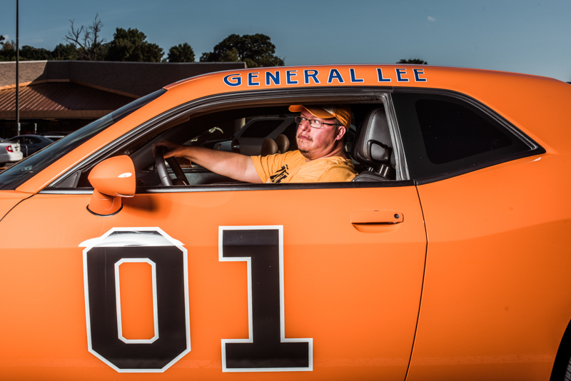 Eric D. Robinson poses for a portrait in his Dodge Challenger at a confederate flag rally held in a parking lot in Seymour, Tennessee on Thursday, July 17, 2015. Host Tom Pierce, and guest, Mathew Heimbach delivered speeches before prompting the group to drive with flags raised through Knoxville. Mike Belleme for Al Jazeera America